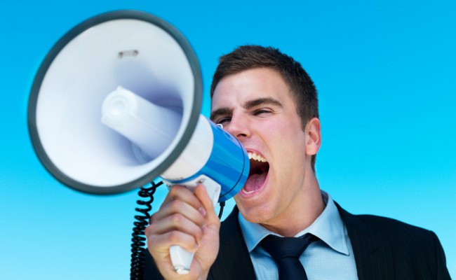 Business man shouting into megaphone with clear sky in the backg
